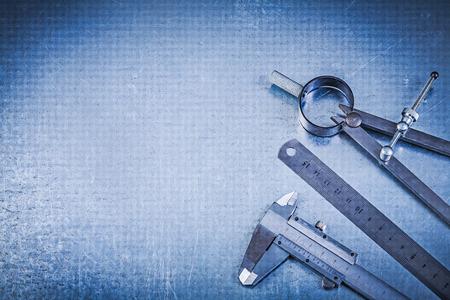 compas de dibujo: Construcci�n del metal Comp�s de dibujo regla con pinza en el fondo met�lico. Foto de archivo