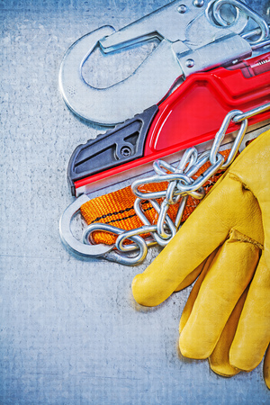 safety harness: Safety harness protective gloves construction level on metallic background.
