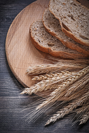 sliced bread: Sliced bread on wooden chopping board bunch of wheat rye ears directly above.