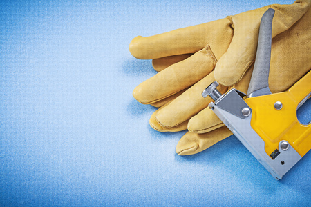 protective gloves: Leather protective gloves staple gun on blue background construction concept.