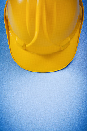 yellow hard hat: Yellow hard hat on blue surface top view construction concept. Stock Photo