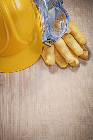 protective spectacles: Hard hat leather protective gloves goggles on wooden board construction concept. Stock Photo