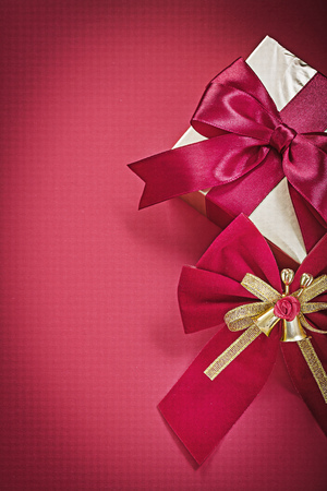 red glittery: Christmas bow gift box on red surface holidays concept.