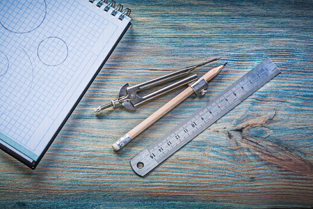 copybook: Checked copybook ruler divider pencil on vintage wood board.