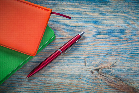 note books: Closed note books pen on vintage wood board education concept.
