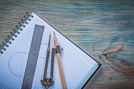 compas de dibujo: A cuadros cuaderno gobernante lápiz de dibujo brújula en la tabla de madera de la vendimia.