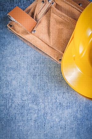 tool belt: Tool belt safety building helmet on metallic background construction concept. Stock Photo
