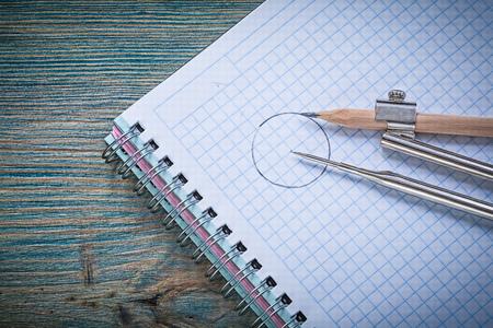 compas de dibujo: Vintage drawing compass pencil checked copybook on wood board construction concept.