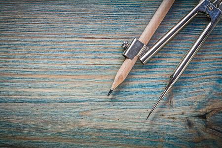 compas de dibujo: Vintage drawing compass pencil on wooden board construction concept.