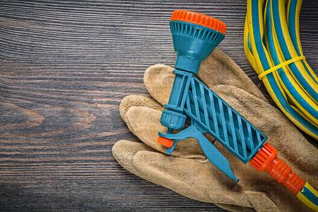Garden rubber hose water sprinkler safety gloves on wooden board gardening concept.