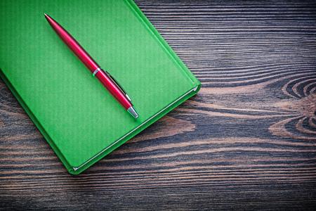 ballpoint: Green notepad ballpoint pen on vintage wood board education concept.