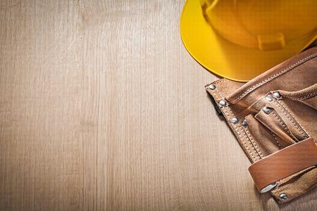 tool belt: Set of tool belt hard hat on wooden board.