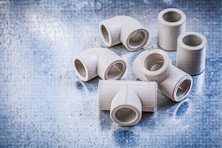 Plastic pipe fittings on metallic surface construction concept.