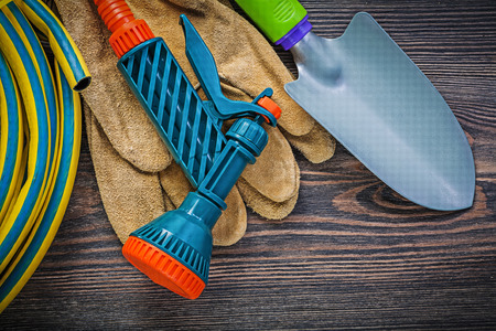 coiled: Coiled garden rubber hose protective gloves hand shovel on wood board gardening concept.