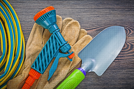 coiled: Coiled garden rubber hose leather safety gloves hand shovel on wood board gardening concept. Stock Photo