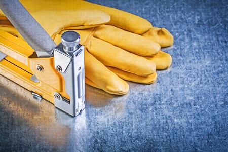 staple gun: Yellow leather safety gloves construction staple on metallic background.