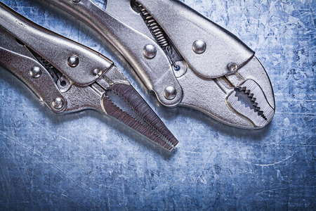 fix jaw: Lock jaw pliers on metallic background construction concept.