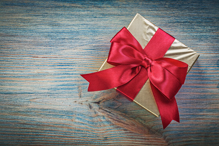 wrapped present: Wrapped present box on vintage wooden board top view holidays concept. Stock Photo