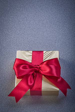 glittery: Present box wrapped in glittery paper with red bow on grey background holidays concept.