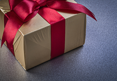 red glittery: Giftbox in glittery paper with red bow on grey background holidays concept. Stock Photo