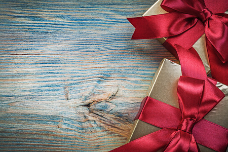 glittery: Giftboxes in glittery wrapping paper on vintage wooden board holidays concept.