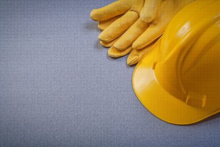protective gloves: Yellow building helmet leather protective gloves on grey background construction concept.