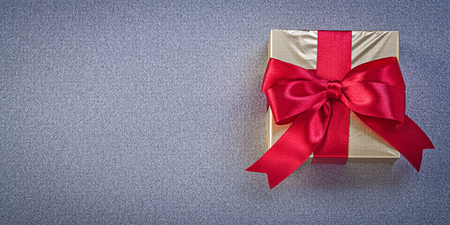red glittery: Wrapped box with presents on grey background holidays concept.