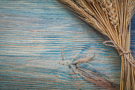 corded: Corded bunch of ripe wheat rye ears on vintage wood board. Stock Photo