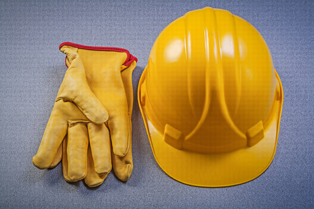 safety gloves: Yellow hard hat safety gloves on grey background construction concept.