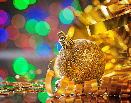 the tinsel: golden christmas ball with rolled tinsel.