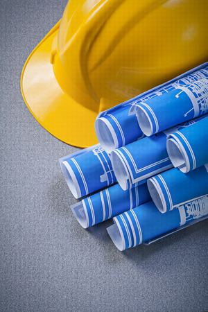 yellow hard hat: Yellow hard hat and blue rolled engineering drawings on grey background Stock Photo