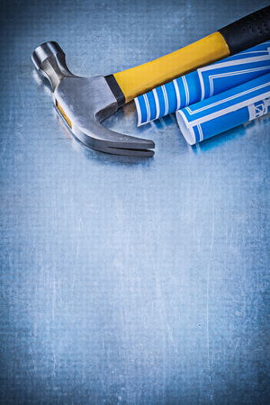 blue metallic background: Blue construction drawings and claw hammer on metallic background Stock Photo