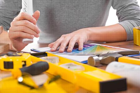 manos del diseñador en la paleta de color y otras herramientas.