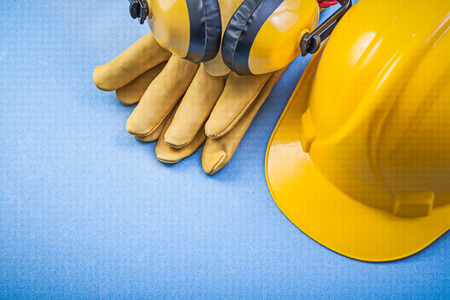 building safety: Earmuffs safety gloves building helmet on blue background construction concept.