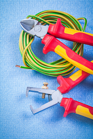 dielectric: Insulation strippers and electrical cable nippers on blue background