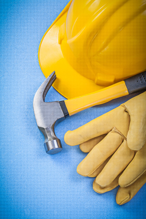 hard hat: Claw hammer, safety gloves and hard hat on blue background