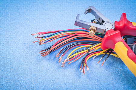 electric blue: Insulated wire strippers set of electric cables on blue background