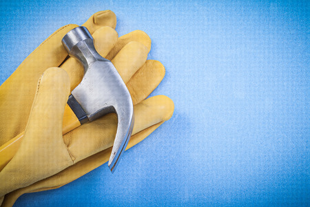 claw hammer: Claw hammer and pair of safety gloves on blue background
