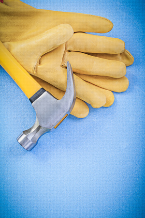 claw hammer: Claw hammer and leather protective gloves on blue background Stock Photo