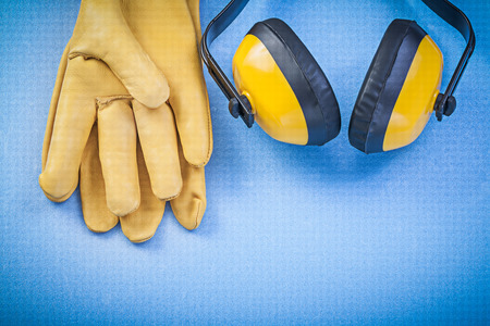 protectors: Ear protectors and safety gloves on blue background
