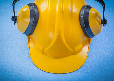ear muffs: Ear muffs hard hat on blue background construction concept. Stock Photo