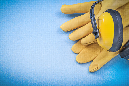 ear muffs: Ear muffs and leather protective gloves on blue background Stock Photo