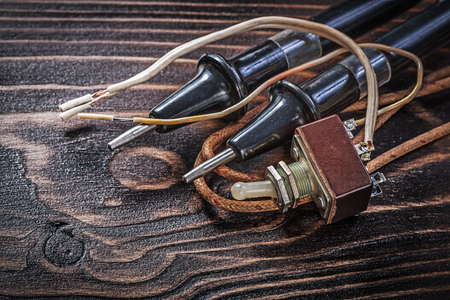 dielectric: Electric toggle switch and vintage electrical tester on wooden board Stock Photo