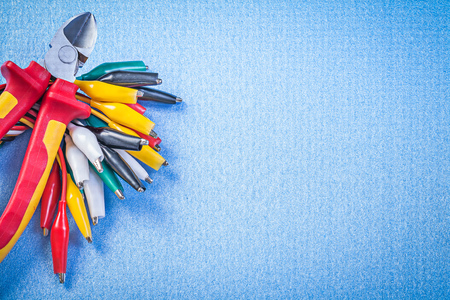 dielectric: Set of multicolored cable crocodiles and cutting pliers on blue background.