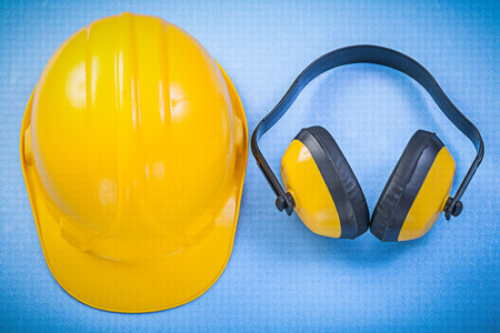 Earmuffs: Safety earmuffs and hard hat on blue background Stock Photo