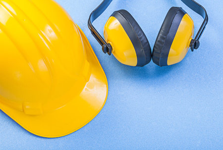 Earmuffs: Safety earmuffs and building helmet on blue background