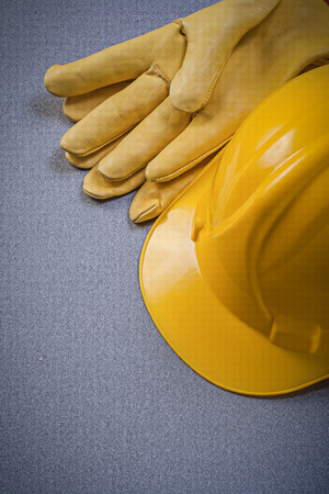yellow hard hat: Yellow hard hat and leather protective gloves on grey background