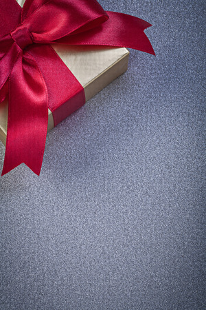 wrapped present: Wrapped present box with red knot on grey background