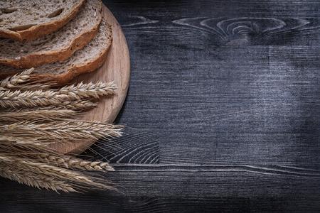 Sliced brown bread on wooden chopping board wheat rye ears copy space.