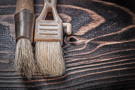 repaint: Age-old paintbrushes on wooden board horizontal version construction concept.